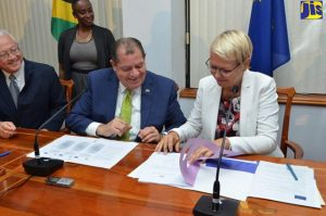 Justice Minister, Hon. Delroy Chuck (left), looks on as Finance and Public Service Minister, Hon. Audley Shaw (centre), and Head of the European Union (EU) Delegation in Jamaica, Ambassador Malgorzata Wasilewska, peruse details of the agreement formalising the EU's provision of approximately $3.3 billion (€22 million) in grant funding for Jamaica's Justice Reform Programme. The agreement was signed during a ceremony at the Finance Ministry in Kingston, on December 8. Overseeing the proceeding is the Finance Ministry's Communications Director, Elaine Oxamendi-Vicet. (Photo: Michael Sloley/JIS)