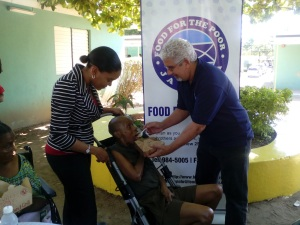 David Mair, Executive Director, Food for the Poor Jamaica feeds Jasmine McKay, a resident of the Golden Age Home during the Christmas treat hosted by his organization on December 8. Mishka Townsend-Brown, Assistant General Manager of the Golden Age Home is at left. (Photo: ProComm)