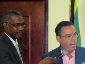 Chief Technical Director in the Ministry of Economic Growth & Job Creation Lt. Col. Oral Khan (left) helps out with the mike as Minister Daryl Vaz speaks. (My photo)
