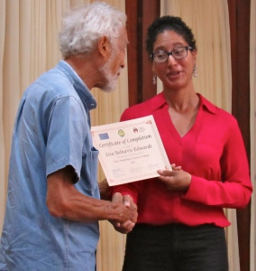 Graduate Lisa Belnavis-Edwards from Woman Inc. receives her certificate from Horace Levy, of the JCSC and Jamaicans for Justice. (My photo)