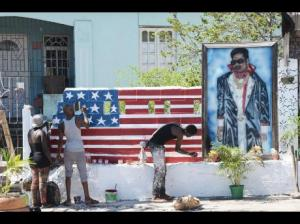 "The FBI is offering a US$100,000 reward for the capture of ""Marlon Jones,"" who may be a Jamaican, for the murder of four people in Los Angeles - including Jamaican gang leader Robert 'Rodigan' Davis - in October. Here are residents of Maxfield Avenue painting a memorial wall for ""Rodigan"" after his death. (Photo: Jamaica Star)"