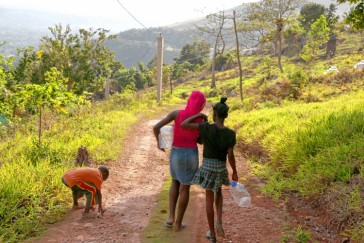 Rural poverty in Jamaica is deep. Here two girls go to collect water, a mile from their home. (Photo: Geoff Forester/Concord Monitor)