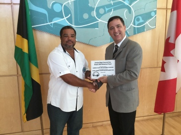 Canadian High Commissioner to Jamaica Sylvain Fabi (right) presents a plaque of appreciation to Brandon Hay, Science Officer/Fish Sanctuary Manager at the Caribbean Coastal Area Management Foundation (C-CAM) at the conclusion of the Portland Bight Protected Area Disaster Risk Reduction Project last week. (Photo: Canadian High Commission/Jamaica)