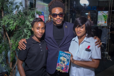 "The superbly talented Mr. Sheldon Shepherd of the band No-Maddz with two friends and a copy of his book ""In the Morning Yah."""