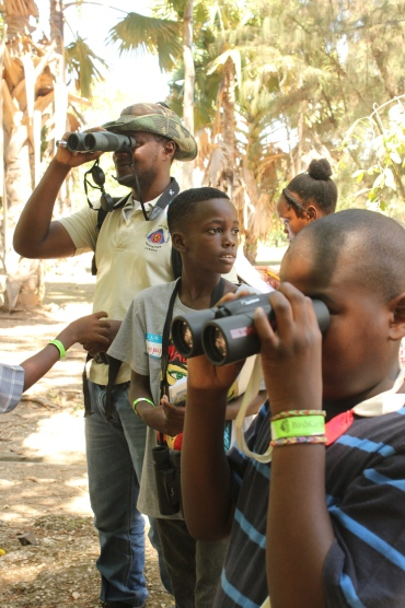 It's not only cameras that focus. Here participants in the BirdSleuth children's camp at Kingston's Hope Zoo two years ago, training their binoculars, before the BirdsCaribbean conference.