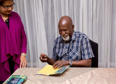 """Professor Mervyn Morris autographs a copy of """"In This Breadfruit Kingdom"""" for Jean Cowrie-Chin (herself a published poet) at the book launch recently."""