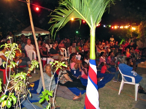 Music is a bridge between people. This is a photo of a memorable evening - the annual Fete de la Musique at Alliance Francaise de Jamaique in 2013. There is no beautiful lawn to sit on or trees to enjoy now, since AFJ was forced to move. (My photo)
