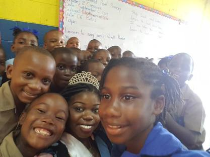 Climate change activist and Miss Jamaica Festival Queen Dainalyn Swaby (she with the crown) cuddles up with students at Mayfield Park Primary School in Kingston on International Peace Day today. (Facebook)
