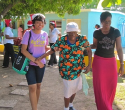 Sometimes it's not so easy to walk... Here JN Foundation volunteers escort a resident of the Golden Age Home in Kingston at a Christmas treat.