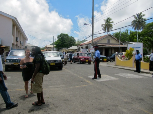 Is the policeman crossing the road at the pedestrian crossing, or...? A scene on the not very busy main street in Carriacou, Grenada.