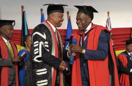 Former senator Floyd Morris receives his doctorate from Professor Hilary Beckles (left) at UWI.