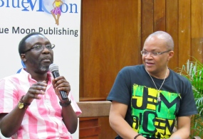 """You can count on comedians to be cheeky. Here is Owen """"Blakka"""" Ellis, making the equally humorous Michael Abrahams laugh at the launch of Blake's book """"Riddim and Riddles"""" published by Blue Banyan Books. (My photo)"""