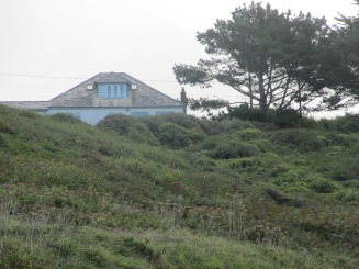 In Cornwall, climbing up from the sea shore, one sees a roof top at the top of the hill.