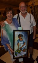 All Smiles At The Auction: John Greaves (right), Director of Tank-Weld Metals and his wife Jennifer Greaves, smile with the beautiful painting of a girl and her avocados, which they bid on at Friends of Food For The Poor Jamaica's 2018 Calendar Launch and Auction on Thursday, November 30, 2017. Food For The Poor held the event in partnership with Young At Art, an art education programme founded and run by Fiona Godfrey. All proceeds from the event will go towards the Savanna-la-Mar Hospital.