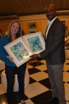 An Artist Hands Over Her Paintings: Nicola Rosen (left), artist and co-owner of Island Art and Framing, hands over her beautiful paintings to bidding winner Dr. Alfred Dawes (right), Chief Medical Officer at Savanna-la-Mar General Hospital at Friends of Food For The Poor Jamaica's 2018 Calendar Launch and Auction on Thursday, November 30, 2017 at the Terra Nova Hotel. The event was held in partnership with Young At Art, an art education programme founded and run by Fiona Godfrey. All proceeds from the event will go towards the Savanna-la-Mar Hospital.