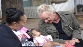 Rock star Sting talks to a little baby at the Bustamante Children's Hospital during a tour with Shaggy, before their fundraising concert.