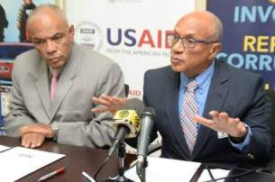 Head of the Major Organised Crime and Anti-Corruption Agency (MOCA) Colonel Desmond Edwards listens as Executive Director of National Integrity Action Trevor Munroe speaks at yesterday's agreement signing between both institutions. (Photo: Jamaica Observer)