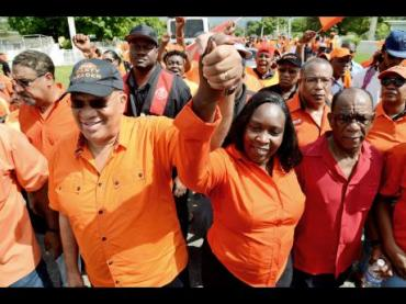 Opposition Leader Peter Phillips holds up the hand of Keisha Hayle, the People's National Party candidate for N.W. St. Andrew, on Nomination Day.