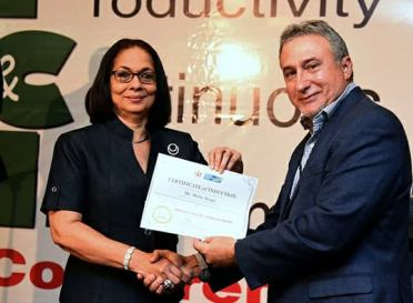Minister of Labour and Social Security Shahine Robinson doing her official part and handing out a certificate to Mr. Metry Seaga. (Photo: Facebook)