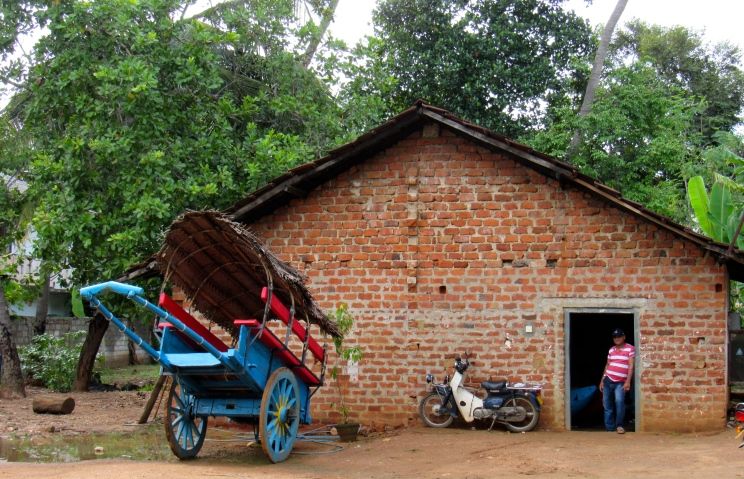 Back in rural Sri Lanka, I saw this brick home. Who did the motorbike belong to? What was this family's story? Did they use the bullock cart?