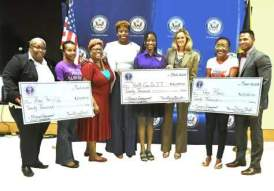 Representatives of three women's organisations that recently received funding from the U.S. Embassy pose with their cheques. Far right is Public Affairs Officer at the U.S. Embassy Jeremiah Knight.