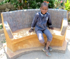 Five-year-old Ajai sits on a bench made of entirely recycled materials at 360 Recycle. And smiles.