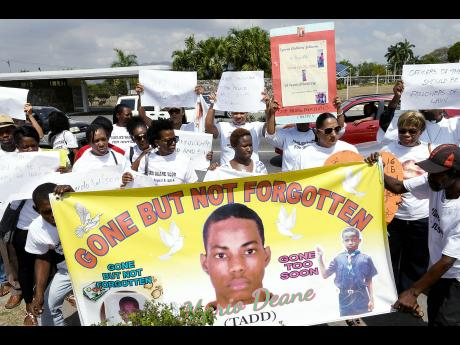 Prostesters carrying a banner with the image of Mario Deane, who died from injuries sustained allegedly from detainees while in a police lock-up in Montego Bay in August 2014. The protests took place before Jamaica House in St Andrew on March 15, 2018, which was observed as International Day Against Police Brutality. (Photo: Norman Grindley/Gleaner)