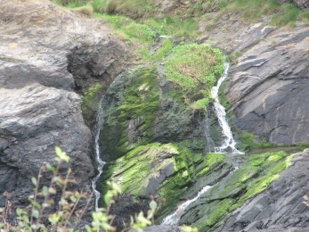 Small waterfalls take twists and turns down the rock face, in north Cornwall.