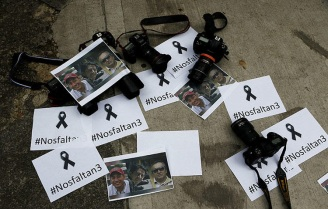 Colombian photographers leave the cameras on the floor in front of the Ecuadorean embassy to protest against the murder of journalist Javier Ortega, photographer Paul Rivas and their driver Efrain Segarra in Bogota, Colombia April 16, 2018. Picture taken April 16, 2018. REUTERS/Jaime Saldarriaga - RC144313D6B0