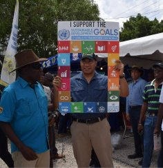 "Prime Minister Andrew Holness looked through an ""SDG window"" at Denbigh Agricultural Show, in support of the UN and other booths focusing on climate change."