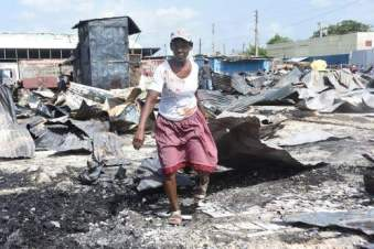 """A woman picks her way through the Ray Ray Market in downtown Kingston, which burned down early Tuesday morning. There have been too many fires in markets over the past year or so. Hopefully at least some of the vendors, who are busy with """"back to school"""" sales, will be compensated. (Photo: Garfield Robinson/Jamaica Observer)"""