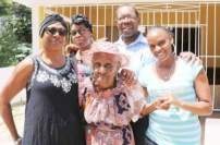 100 years old! Edith McPherson (centre) with (from left) Yvonne McPherson Reynolds, daughter; Terica Brown Abrahams, granddaughter; Ray Howell, son; and Shameke Mason, granddaughter. Ms. McPherson, of Glengoffe, St. Catherine, was congratulated by the Queen recently. (photo: Jason Tulloch/Jamaica Observer)