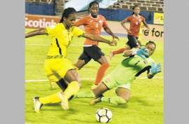 Jamaica's Khadija Shaw (left) lines up to fire past Trinidad and Tobago's goalkeeper Kimika Forbes during their CONCACAF Caribbean Women's Qualifier inside National Stadium on Friday. Jamaica won 4-1. (Photo: Norman Thomas)