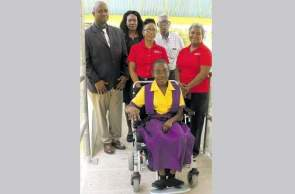 Britannia Stephenson (in wheelchair) is joined by Digicel Foundation's education and special needs programme officer, Jennifer Spence Silvera (front row, left) and CEO Karlene Dawson (second left) as well as (back row, from left) Hopewell High principal Byron Grant, Britannia's mother Cecilia Hill and Hopewell High board chairman Jeremiah Dehaney on one of the ramps at the state-run school on Monday. (Photos: Philp Lemonte)